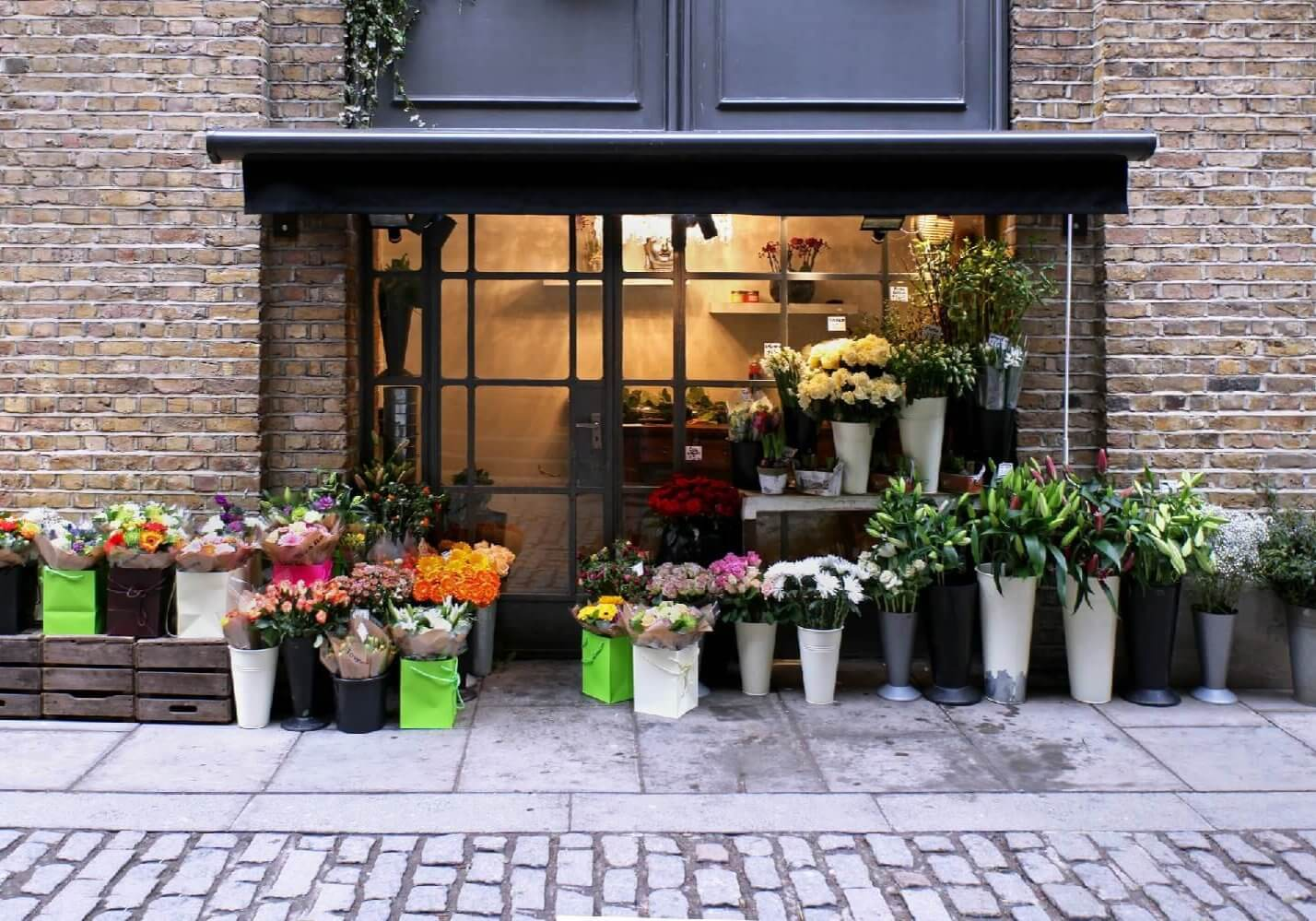 Flower shop exterior in street with brickwall facade